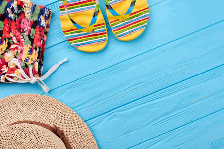 Summer holiday fashion concept. Woman beach clothing, blue wooden background. Stock Photo