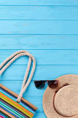Textile handbag, hat, sunglasses. Beach accessories, vintage wooden background. Stock Photo
