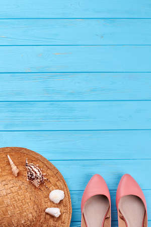 Summer vacation background, blue surface. Female sandals, straw hat, sea shells, retro sea space. Stock Photo