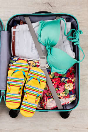 Bright summer stuff in suitcase. Full opened suitcase with clothing, wooden background. Stock Photo