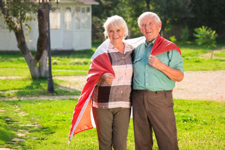 Elderly couple wrapped in flag. Smiling woman and man outdoor. Generation of the proud.