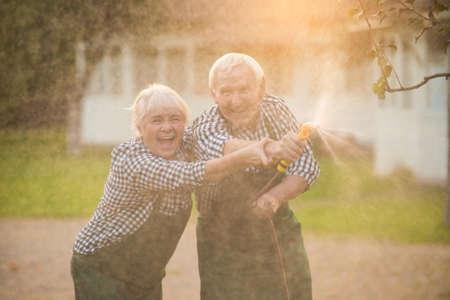 Oud paar met tuinslang. Vrolijke vrouw en man buitenshuis. Stockfoto