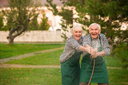Old couple having fun. Happy people with garden hose. Stockfoto