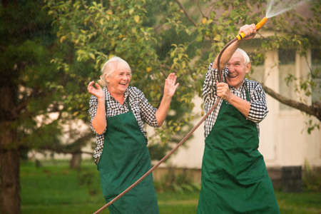 Cheerful people outdoors. Couple with garden hose. 스톡 콘텐츠