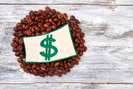 Note with dollar, wooden background. Coffee beans and image.