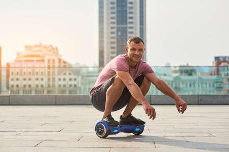 Glimlachende man op hoverboard. Kerel in de stad.