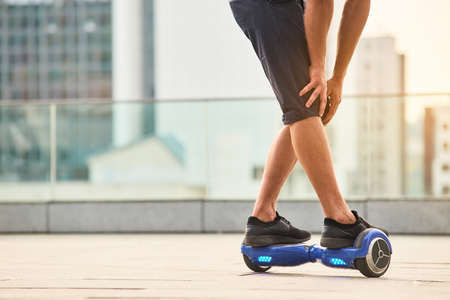 Legs of man riding hoverboard. Blue gyroscooter outdoors.