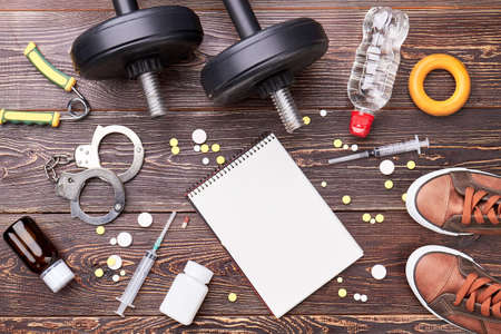 expander: Paper notebook, syringe, dumbbells, handcuffs. Illegal pills in sport activity.