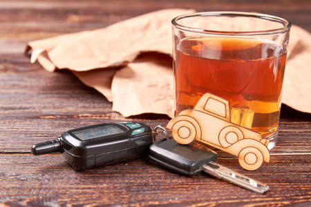 Car, whisky, automobile keys. Brandy with ice, car, automobile keys on wooden background. Concept of drunk drivers accidents. Stock Photo