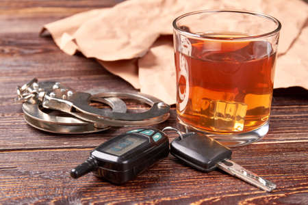 designated: Handcuffs, car keys, whisky glass. Glass of alcohol, metal handcuffs, keys close up. Driver and alcohol is big irresponsibility.