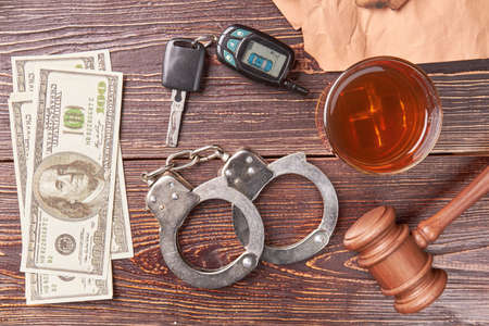 Money, handcuffs, whiskey, key, gavel. Pair of handcuffs, car keys, dollars, gavel, alcohol, top view. The concept of drink driving.