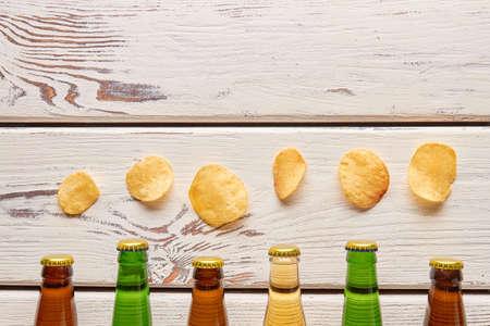 bottlenecks: Chips above beer bottlenecks, wooden background. Harmful habits dangerous for life.