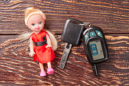 Little doll and car key isolated. Doll in red beside keys from car on old wooden background, top view.