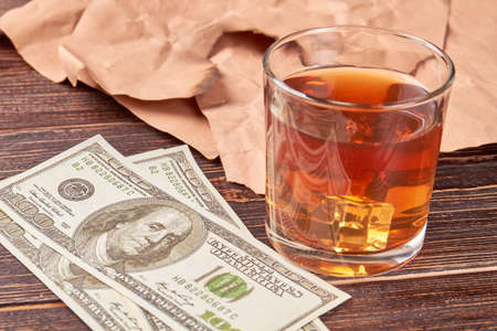 Dollars, glass of whiskey, paper, wooden background. Still life money and alcohol.