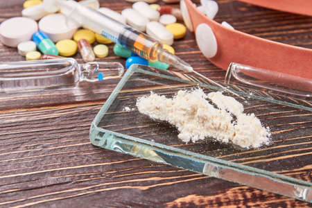 Drugs overdose leads to death. White powder on glass. Syringe, pills, wooden background.