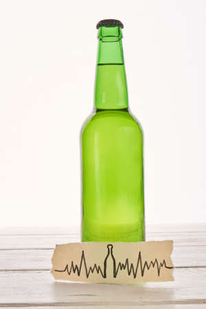 Abuse of alcohol harmful for heart. Image of cardiac impulses, bottle of beer. Stock fotó