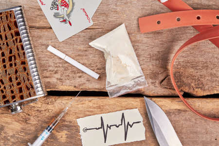 rid: Alcoholism and narcotics background. Drugs, belt, cards, alcohol, cigarette, top view. Stock Photo