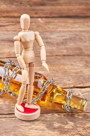 Alcohol bottle wrapped with metal chain. Human wooden dummy, bottle with chain, wooden background. Concept of alcohol addiction. Stock Photo