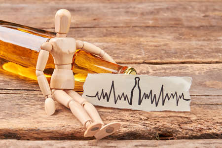 Human wooden figurine, alcohol beverage. Wooden dummy, image of heart beat, wooden background. Stock Photo