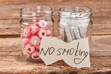 No smoking concept. Glass jars with candies and tobacco cigarettes, paper massage, wooden background.