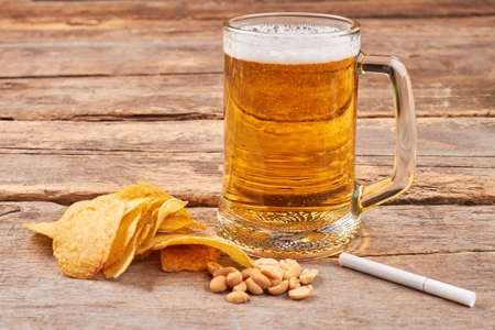 Glass of beer, chips, nuts, cigarette. Concept of beer addiction and unhealthy lifestyle. Stock Photo