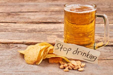 ビールの概念を飲むを停止します。ポテトチップス、ピーナッツ、ビール、メモ、古い木製のテーブルのマグカップ。