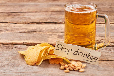 gastro: Stop drinking beer concept. Potato chips, peanuts, mug of beer, note, old wooden table.