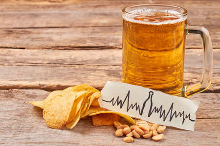 Beer addiction leads to heart disease. Potato chips, nuts, transparent mug of beer, image of heartbeat, wooden table.