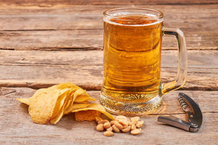 Glass of beer, chips, nuts, corkscrew. Concept of beer addiction. Stock Photo