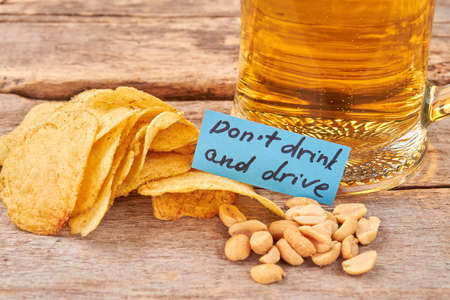 Do not drink and drive concept. Beer background, paper message.