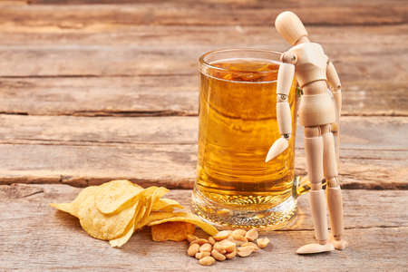 Human wooden dummy and glass of beer. Potato chips, nuts, glass of beer, human wooden dummy, wooden background. Stock Photo