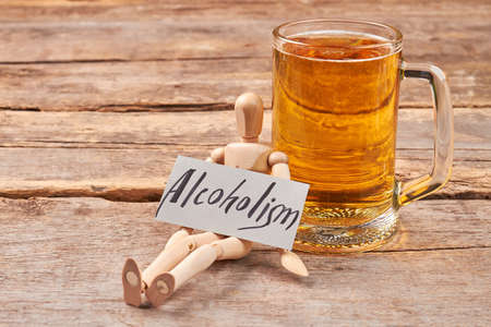 Alcoholism kills organism. Human wooden dummy with paper message near mug with beer.
