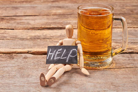 Help to get rid of alcohol. Human wooden figurine with message help, glass of beer, old wooden background. Archivio Fotografico