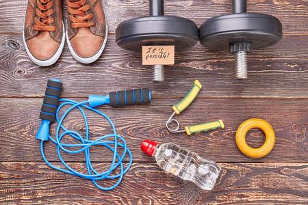 Sportsman equipment for physical training. Shoes, dumbbells, jumping rope, expander, bottle, wooden floor.