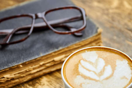 smarter: Coffee, old book and glasses. Latte with foam close up. Can coffee make you smarter.