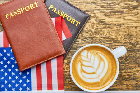 Coffee, passports and US flag. White latte cup top view. American citizenship requirements. Stock Photo