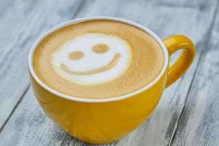 Smiley latte art. Yellow coffee cup close up. Does caffeine make you happy. Foto de archivo