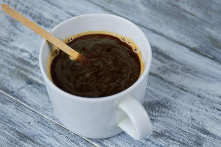 Donkere koffie en roerstok. Espresso op houten tafel.