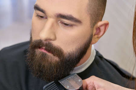 hair stylist: Close up of beard grooming. Barber using trimmer.