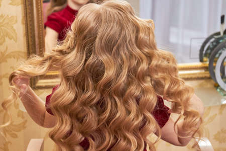 golden rule: Beautiful hair of little girl. Wavy blonde hair. Golden rules of hair care.