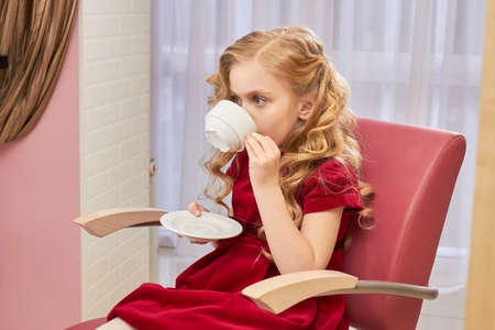 hair stylist: Little girl with beautiful curly blonde hair is drinking coffee