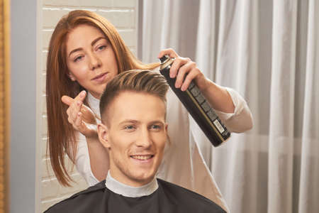 Smiling guy at the barber. Stylist holding hair spray bottle. Best natural hairspray reviews.