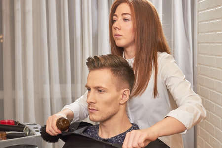 Barber woman with her customer. Caucasian male in hair salon.