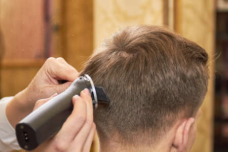 hair stylist: Man getting haircut close up. Hands, comb and hair clipper. Stock Photo