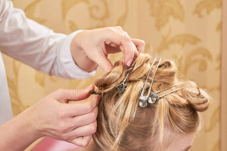 Hands of female hairstylist working. Blonde hair and hairpins.