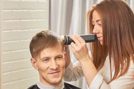 appliances: Smiling man at the barber. Stylist using hair clipper.