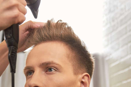 appliances: Barber drying hair, close up. Male hair and blow dryer.