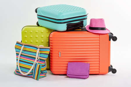 Clutch bag, pink hat, suitcases. Woman summer pocketbook and beach accessories. Stock Photo