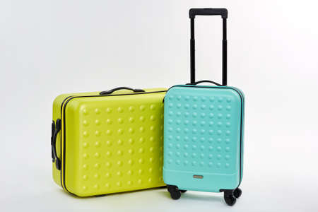 Close up of wheeled suitcases. Bright summer luggage, white background. Cases for journey.