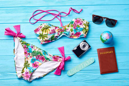 beachfront: Swimsuit and accessories for going abroad. Colorful female swimsuit for rest in south. Stock Photo